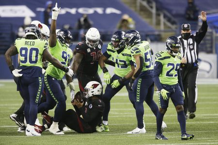 <span>Seattle Seahawks players celebrate after Arizona Cardinals quarterback Kyler Murray, lower-center, was tackled during the first half of an NFL football game, Thursday, Nov. 19, 2020, in Seattle. (AP Photo/Lindsey Wasson)</span>