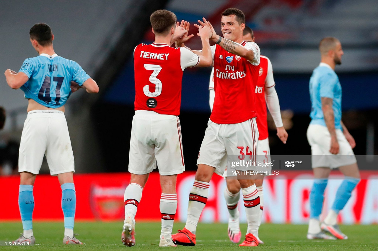 Arsenal's Scottish defender Kieran Tierney (C) and Arsenal's Swiss midfielder Granit Xhaka (R) celebrates at the end of the English FA Cup semi-final football match between Arsenal and Manchester City at Wembley Stadium in London, on July 18, 2020. (Photo by MATTHEW CHILDS / POOL / AFP) / NOT FOR MARKETING OR ADVERTISING USE / RESTRICTED TO EDITORIAL USE (Photo by MATTHEW CHILDS/POOL/AFP via Getty Images)