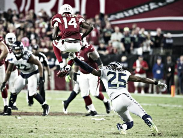 J.J. Nelson leaps over Richard Sherman, running the ball deep into Seattle's territory. |Source: Bettina Hansen / The Seattle Times|