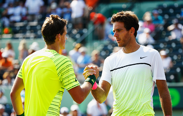 Vasek Pospisil of Canada meets Juan Martin Del Potro of Argentina at the net after defeating him during day 4 of the Miami Open