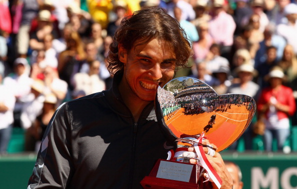 Rafael Nadal bites his eighth Monte Carlo Rolex Masters trophy after his 2012 final win over Novak Djokovic/Getty Images
