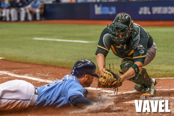 Steve Pearce (left) slides under Stephen Vogt's tag to score the Rays' fifth run of the day. Photo: Bill Howard/VAVEL USA