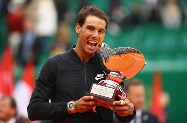Rafael Nadal bites the trophy after winning his record-breaking 10th title in Monte Carlo last year. Photo: Clive Brunskill/Getty Images