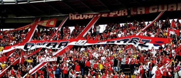 En la tribuna popular se inmortalizó una bandera que lleva su nombre y está presente en cada partido del 'león' en condición de local, y a donde la afición viaja a acompañar al equipo. Imagen: Independiente Santa Fe.