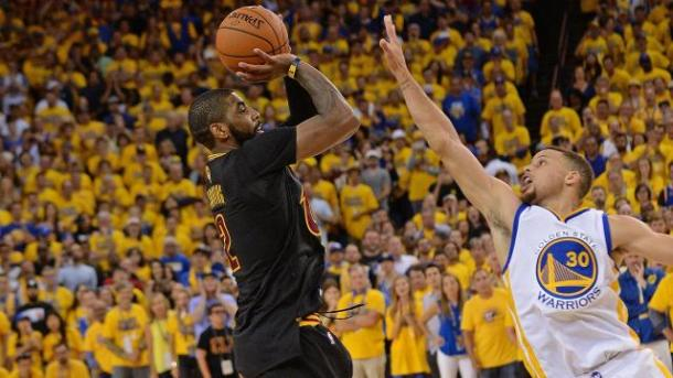 Kyrie Irving in azione di tiro, contestato da Steph Curry