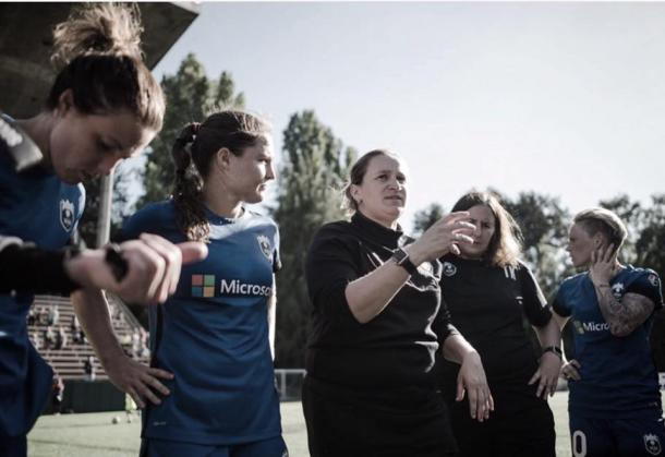 Laura Harvey (center) as defender Kendall Fletcher (left)  listens in on Harvey's coaching advice. Source: Seattle Reign FC