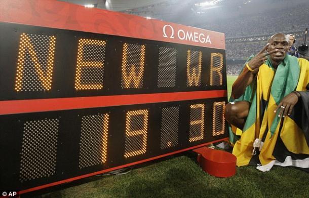 Bolt ao lado do placar eletrônico mostrando o novo recorde mundial dos 200 metros (Foto: AP)