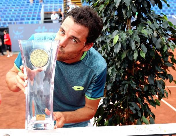 Marco Cecchinato kisses the first tour-level trophy of his career in Budapest. Photo: Xinhua/Attila Volgyi/iANS