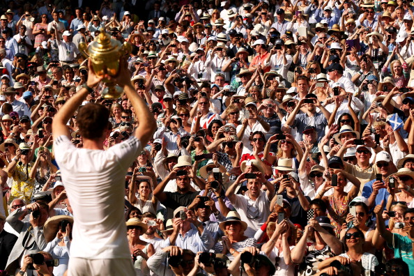 Fans cheer and take photographs as Andy Murray poses with the Gentlemen's Singles Trophy following his victory at Wimbledon 2013. (Photo by Clive Brunskill/Getty Images)