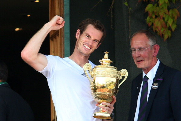 Andy Murray celebrates on the Centre Court balcony as he holds the Gentlemen's Singles Trophy following his victory against Novak Djokovic in Wimbledon. (Photo by Julian Finney/Getty Images)