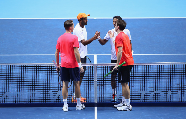 Raven Klaasen and Rajeev Ram congratulate Henri Kontinen and John Peers at the net (Photo: Glyn Kirk/Getty Images)