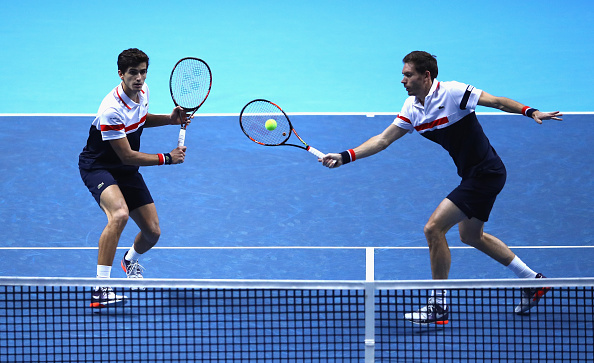 Nicolas Mahut hits a volley at the net next to his partner Pierre-Hugues Herbert (Photo: Alex Pantling/Getty Images)