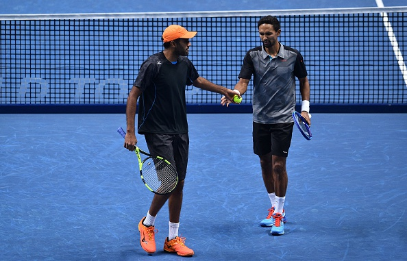 Raven Klaasen and Rajeev Ram touch hands between points against Jamie Murray and his partner Bruno Soares (Photo: Glyn Kirk/Getty Images)
