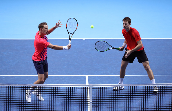 Henri Kontinen hits a volley with John Peers watching (Photo: Julian Finney/Getty Images)