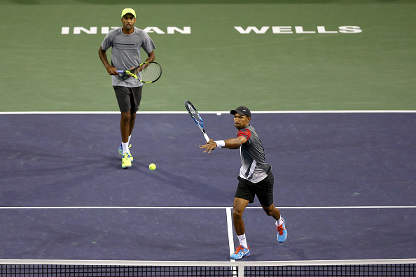 Raven Klaasen smashes a volley at the net with partner Rajeev Ram behind (Photo: Clive Brunskill/Getty Images)