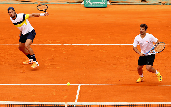 Feliciano Lopez strikes a backhand shot with Marc Lopez heading towards the net (Photo: Clive Brunskill/Getty Images)