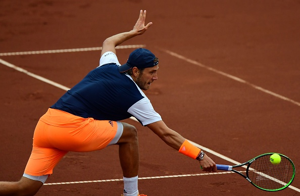 Lucas Pouille hits a return to Martin Klizan (Photo: Attila Kisbenedek/Getty Images)