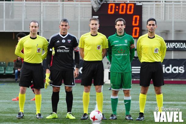 Los capitanes, Txemi y Torrealdai, posan con el trío arbitral antes del partido.