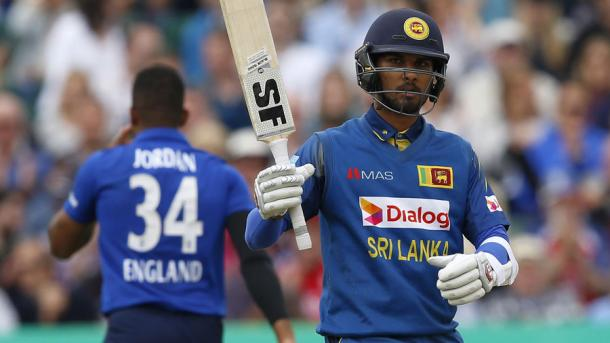 Chandimal holds up his bat during his innings of 62 | Photo: AFP