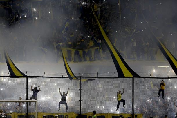 Capos lead Boca Juniors fans in pyrotechnic-filled choreography and cheers ahead of the team's return leg match against River Plate in the 2015 Copa Libertadores round of 16. (Photo credit: Associated Press)