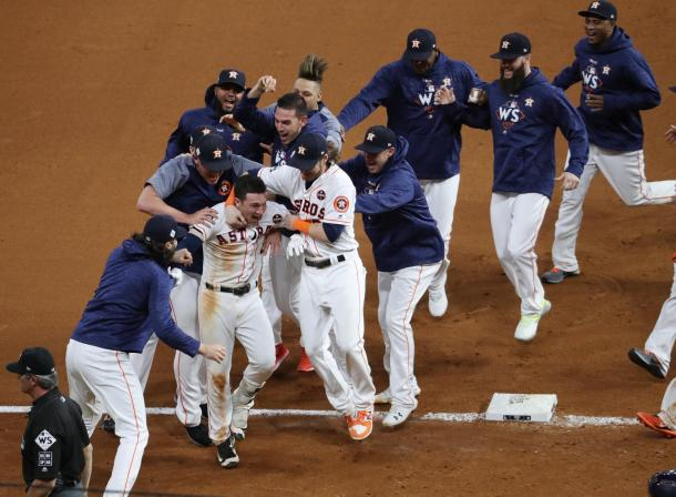 Bregman ids mobbed by teammates after driving in the winning run/Photo: Thomas Shea/Getty Images