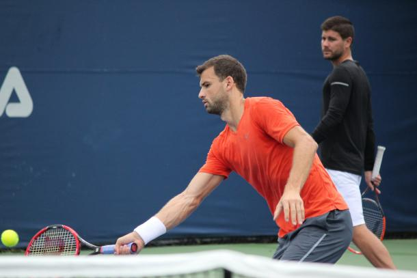 Grigor Dimitrov hits a forehand volley during a practice session with local junior Jack Mingjie Lin at the 2016 Rogers Cup presented by National Bank, under the watchful eye of Daniel Vallverdu. | Photo: Max Gao