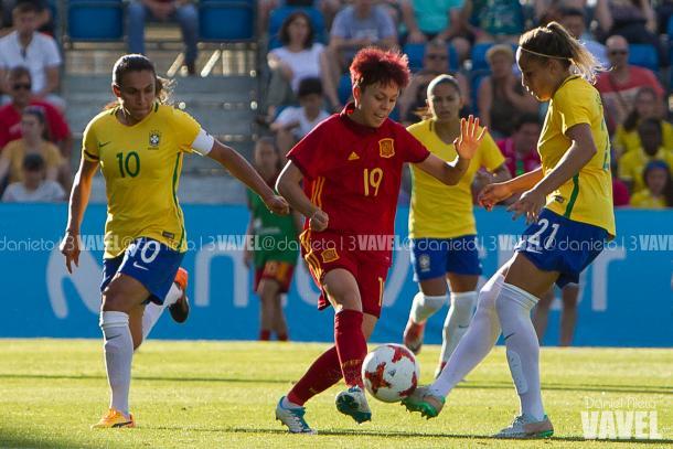 Amanda Sampedro ante dos futbolistas de Brasil en un amistoso / Foto: Daniel Nieto (VAVEL)