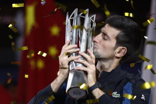 Novak Djokovic kisses his record-breaking fourth trophy in Shanghai. Photo: Andy Wong/AP