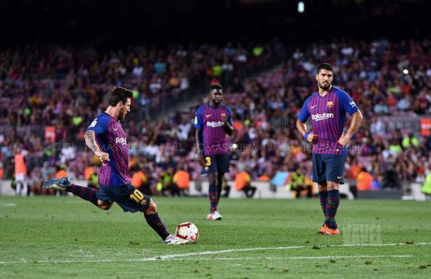 Messi golpea un libre directo ante la mirada de Suárez y Umtiti