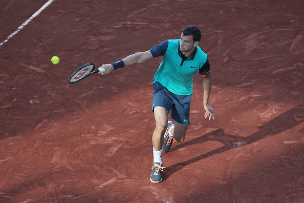 Grigor Dimitrov slides into a backhand at the 2015 TEB BNP Paribas Istanbul Open/Getty Images