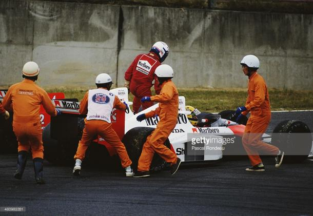 Prost clambers out of his car, whilst Senna looks for help. | Photo: Getty Images/Pascal Rondeau