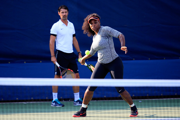 Serena Williams, hits a ball during a practice session as her coach Patrick Mouratoglou looks on prior to the U.S. Open. (Photo by Chris Trotman/Getty Images for the USTA)