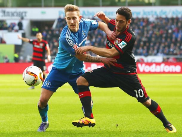 Calhanoglu and Holtby battle for the ball. | Photo: kicker