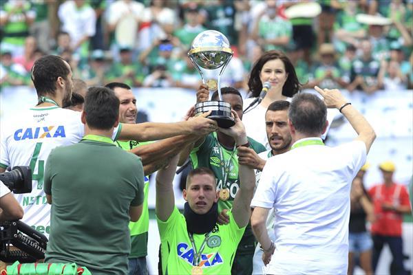 Jackson Follman (centro) levanta la copa junto a los otros sobrevivientes ante una Arena Condá lleno. | Foto: Sebastián Moreira/EFE