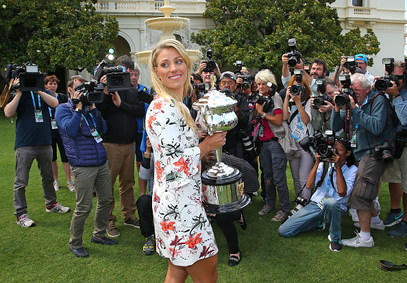 Kerber busy during her photoshoot with the trophy after winning the Australian Open. Photo: Scott Barbour/Getty Images.