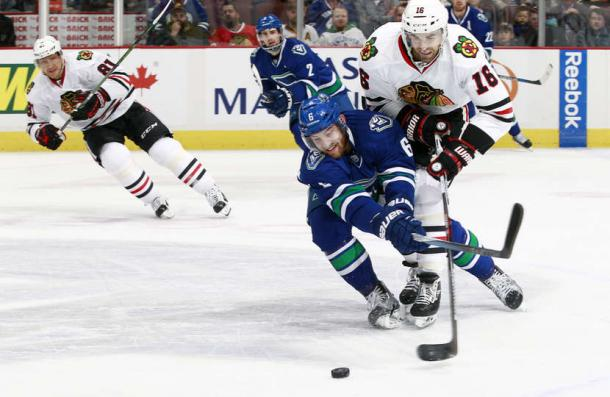 Yannick Weber #6 of the Vancouver Canucks reaches in to check #16 Andrew Ladd of the Blackhawks. Source: Jeff Vinnick- NHLI via Getty Images