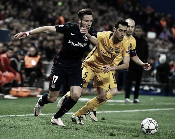 Saúl disputa bola com Busquets em clássico entre Atleti e Barça | Foto: Gerard Julien/Getty Images