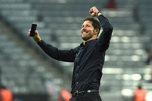 Diego Simeone comemorando classificação com um celular, no centro do gramado da Allianz Arena (Foto: Getty Images)