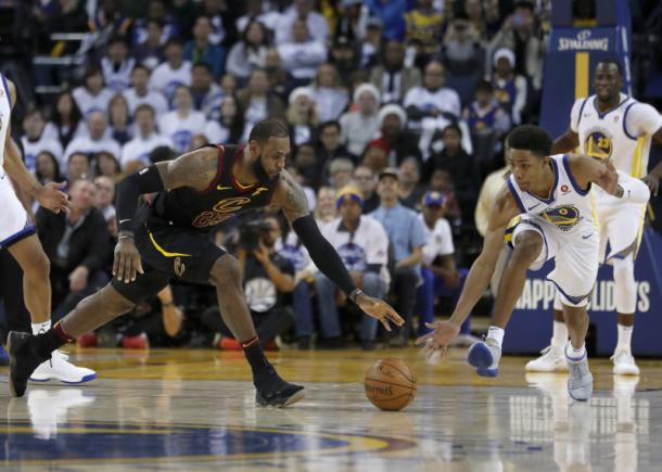 James battles with Golden State's Patrick McCaw for a loose ball during the Cavaliers-Warriors Christmas Day game/Photo: Tony Avelar/Getty Images