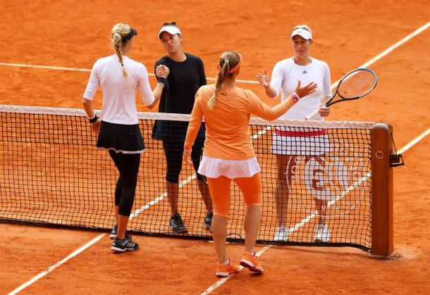 Both teams shake hands at the net after their end of their match. Photo: Julian Finney