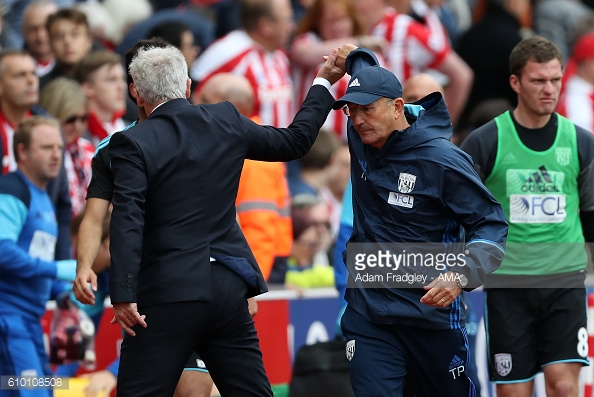Awkward: Hughes and Pulis endure uncomfortable handshake as Baggies snatch late point (photo:getty)