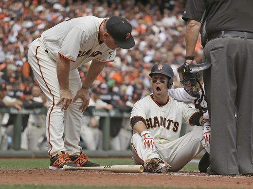 Giants manager Bruce Bochy, left, checks Buster Posey on the ground after he was hit by a Taijuan Walker pitch in the first inning of Monday's game. (Photo: Eric Risberg/AP)