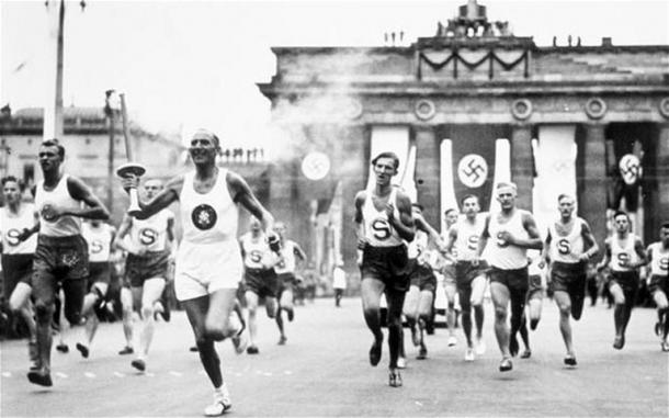 Tocha olímpica sendo carregada em Unten den Liden, atrás o Portão de Brandemburgo/ Foto: Olympic/ Divulgação
