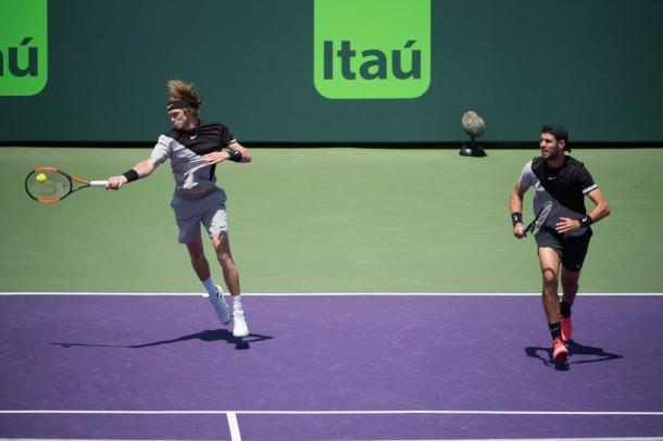 Andrey Rublev strikes a forehand shot with Karen Khachanov looking on (Photo: @MiamiOpen)