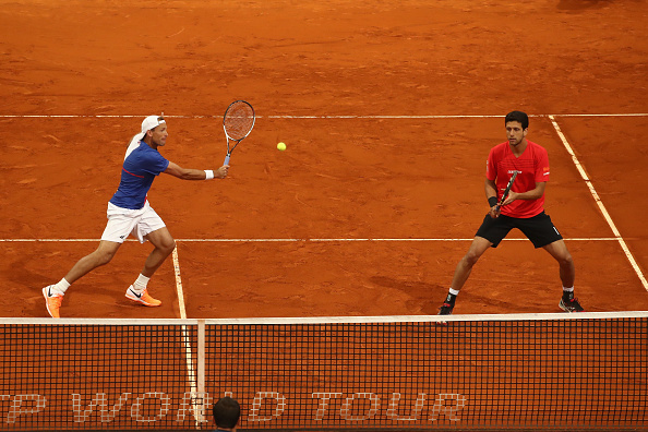Lukasz Kubot strikes a volley with Marcelo Melo looking on (Photo: Julian Finney/Getty Images)