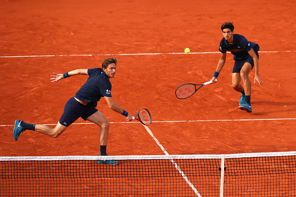 Pierre-Hugues Herbert and Nico Mahut return the ball to Oliver Marach and Mate Pavic (Photo: Clive Brunskill/Getty Images)