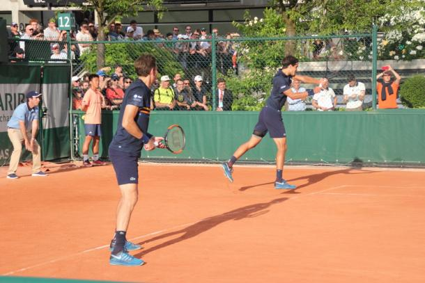Pierre-Hugues Herbert strikes a backhand shot with partner Nico Mahut watching on (Twitter)