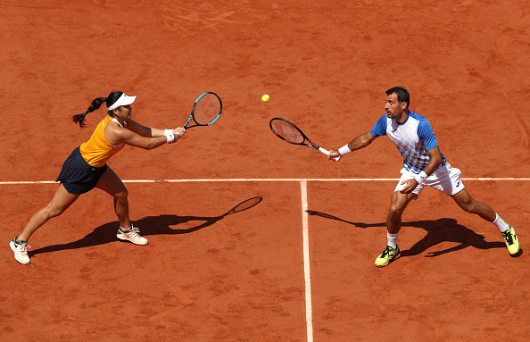 Latisha Chan and Ivan Dodig attempt to return the ball (Photo: Matthew Stockman/Getty Images)