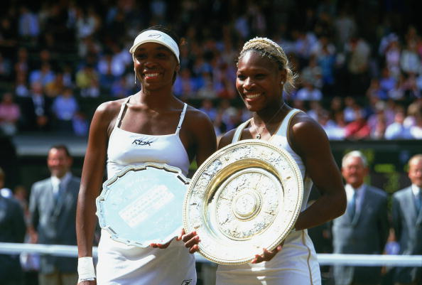 Serena Williams (R) poses with her sister Venus Williams (L) after winning her first Wimbledon title in 2002. (Photo by Mike Hewitt/Getty Images)