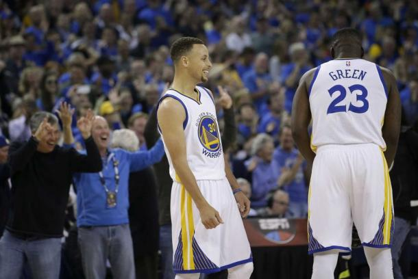 Stephen Curry and Draymond Green smile in celebration after a three pointer during their record setting win on Wednesday (AP Photo/Marcio Jose Sanchez)